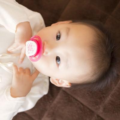 「おしゃぶりを咥えて横になる赤ちゃん」の写真素材