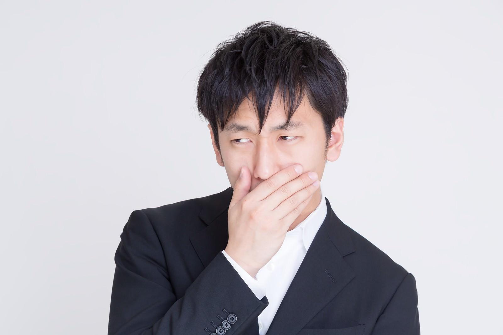 「年収低すぎて口に手をあてるビジネスマン」の写真[モデル:大川竜弥]