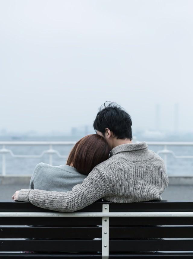 ベンチで肩を寄せ合う恋人の写真