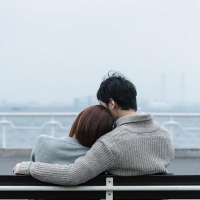 「ベンチで肩を寄せ合う恋人」の写真素材