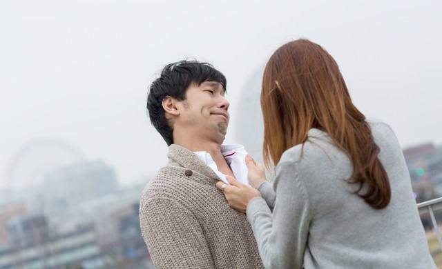 女性に胸倉を掴まれた全然反省していない男性の写真
