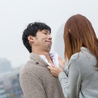 「女性に胸倉を掴まれた全然反省していない男性」の写真素材