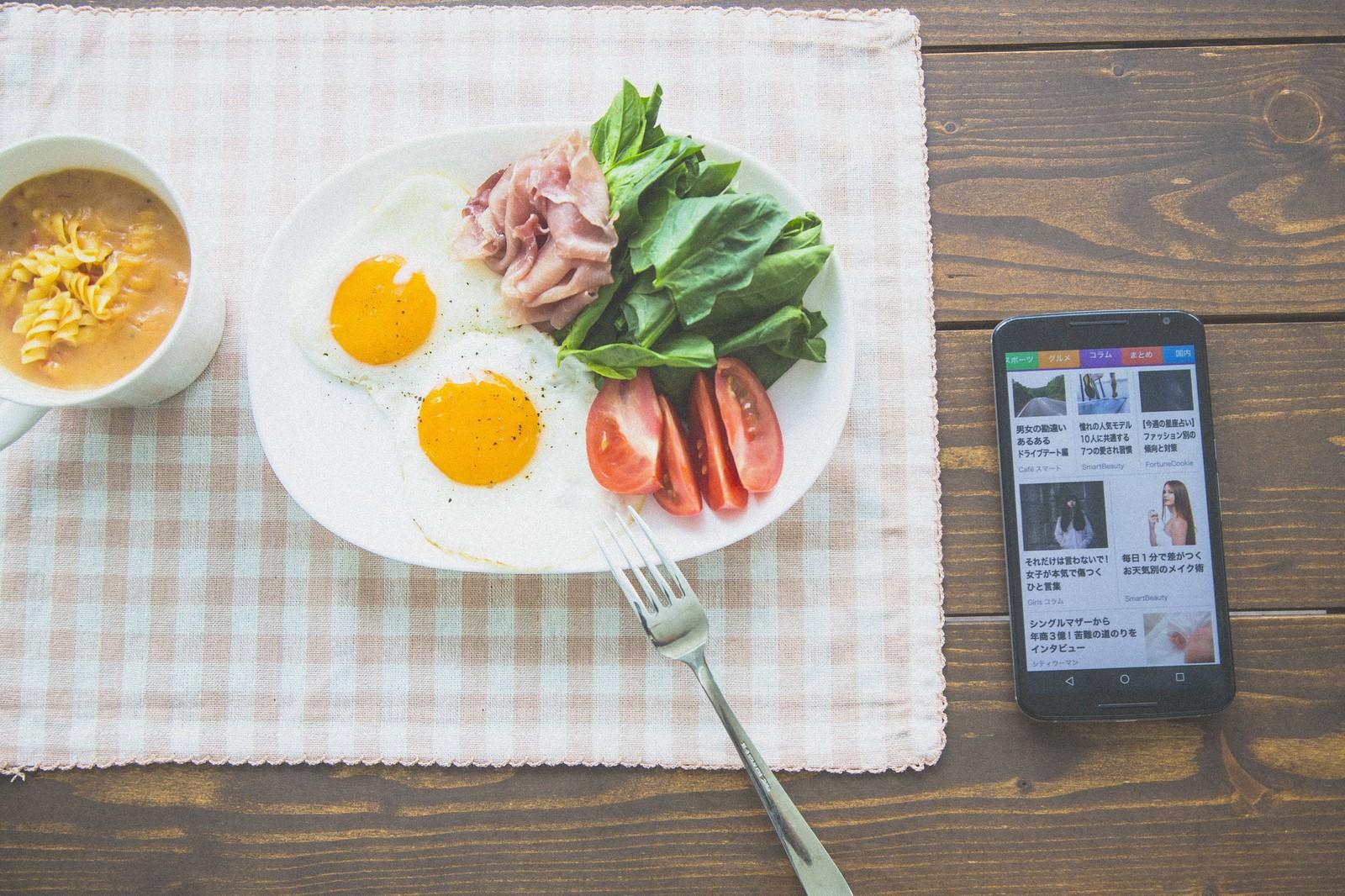「ニュースを見ながら朝食を食べるニュースを見ながら朝食を食べる」のフリー写真素材を拡大