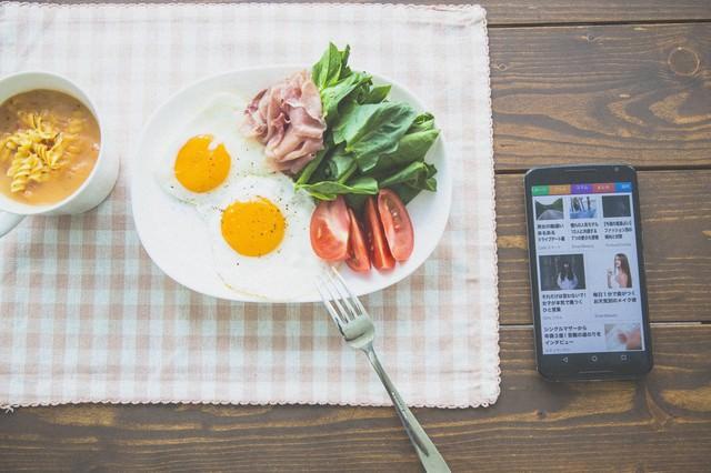 ニュースを見ながら朝食を食べるの写真