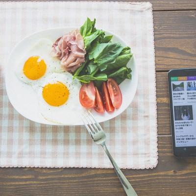 「ニュースを見ながら朝食を食べる」の写真素材