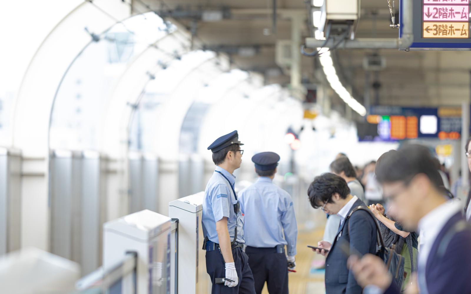 「電車を待つ人と駅員」の写真