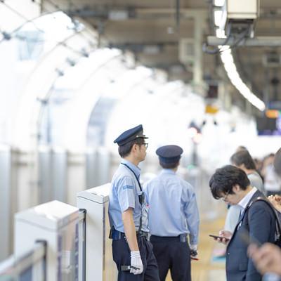 電車を待つ人と駅員の写真