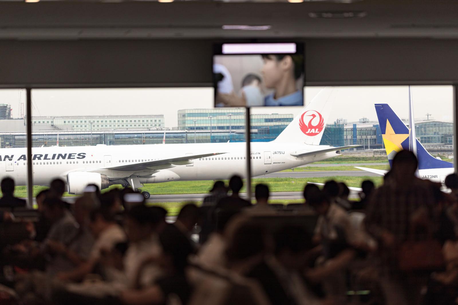 「空港の出発ロビーで待つ人々」の写真