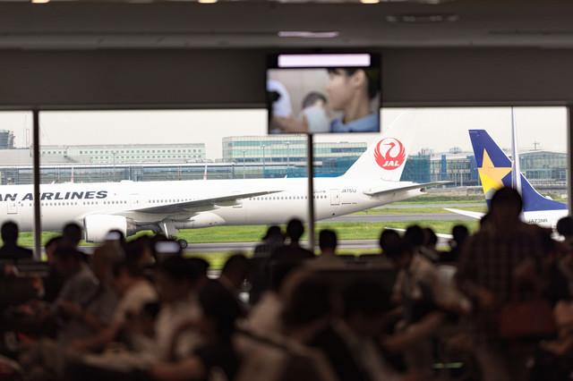 空港の出発ロビーで待つ人々の写真