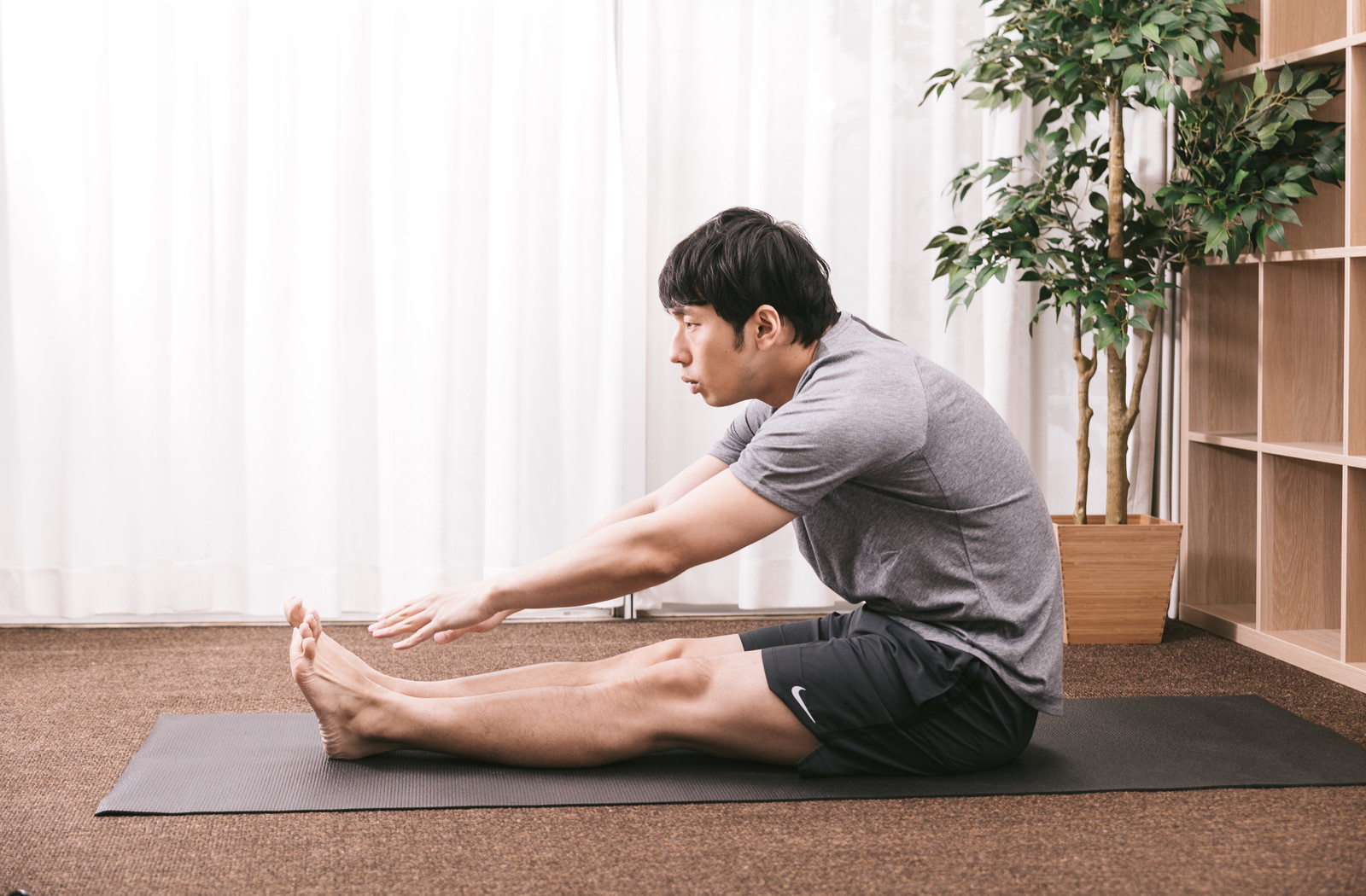 「前屈ができない体の硬い男性」の写真[モデル:大川竜弥]