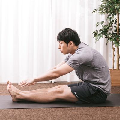 「前屈ができない体の硬い男性」の写真素材
