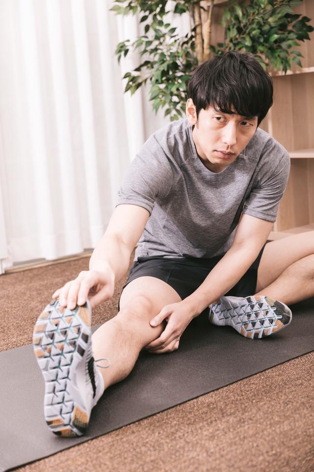 入念に準備運動をするスポーツマンの写真