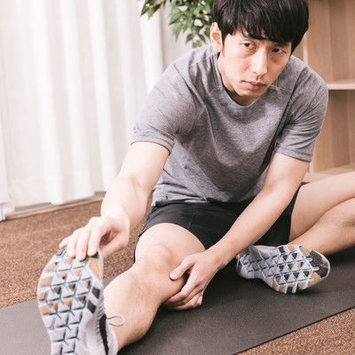 「入念に準備運動をするスポーツマン」の写真素材