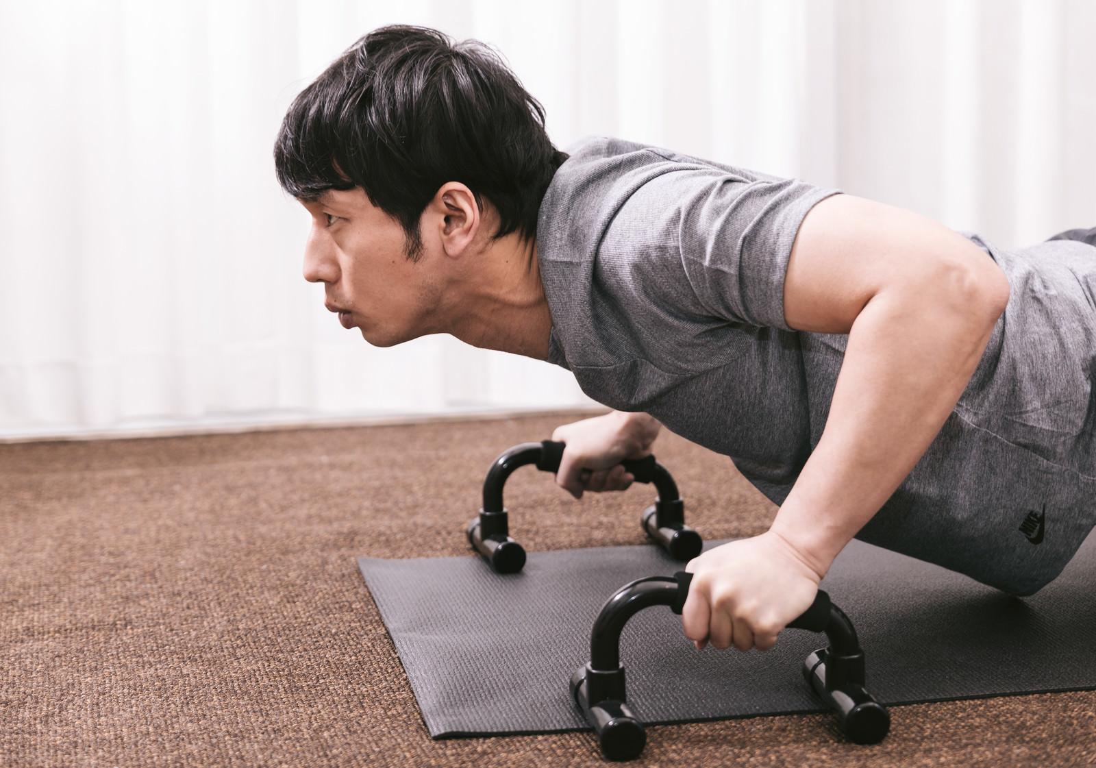 「プッシュアップバーで大胸筋を鍛える男性」の写真[モデル:大川竜弥]