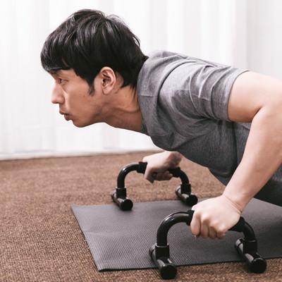 「プッシュアップバーで大胸筋を鍛える男性」の写真素材