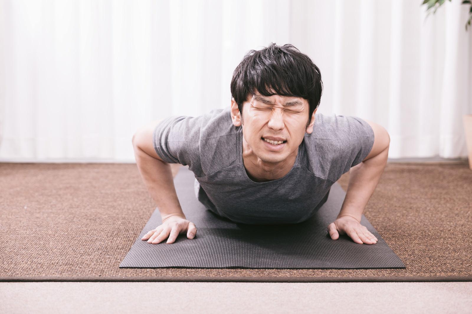 「疲労物質が溜まり苦痛に顔を歪める男性」の写真[モデル:大川竜弥]