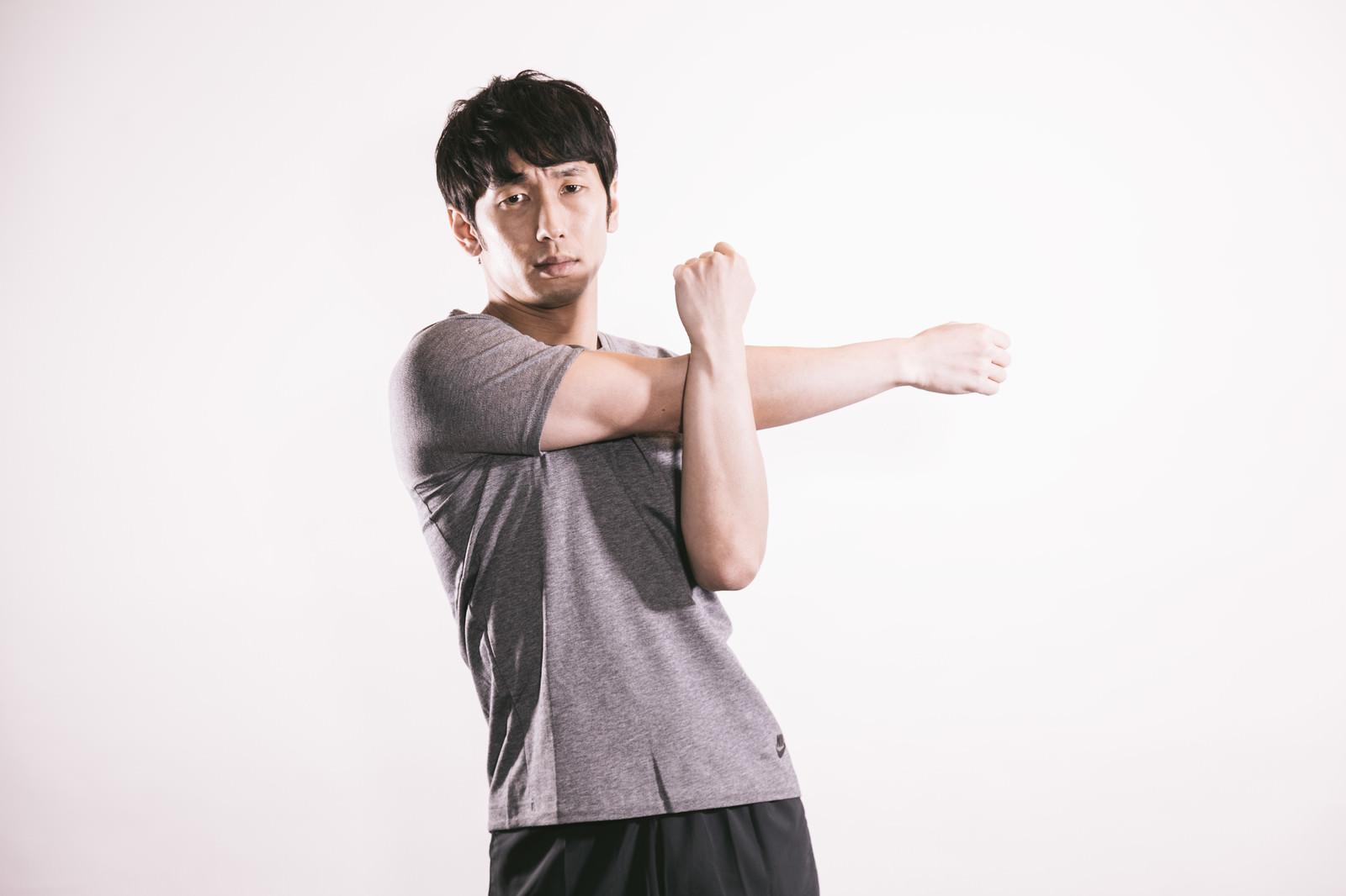 「上腕三頭筋を伸ばす男性」の写真[モデル:大川竜弥]