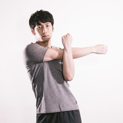 上腕三頭筋を伸ばす男性の写真