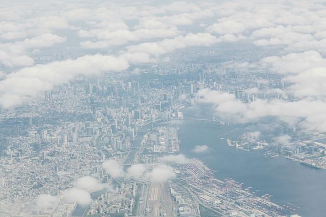 雲の切れ目から見える東京の高層ビル郡の写真