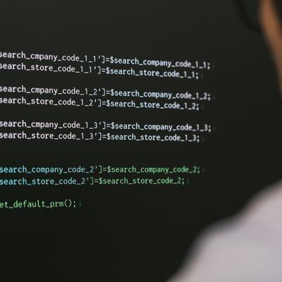 「残業中PHPコードを書くシステムエンジニア」の写真素材