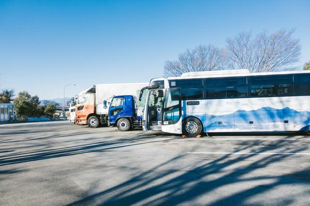 高速のパーキングに停車中のバスと大型トラックの写真