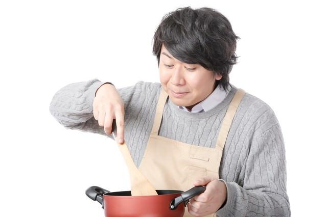 鍋に入ったスープをかき混ぜる料理研究家の写真