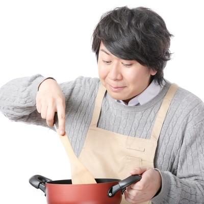「鍋に入ったスープをかき混ぜる料理研究家」の写真素材