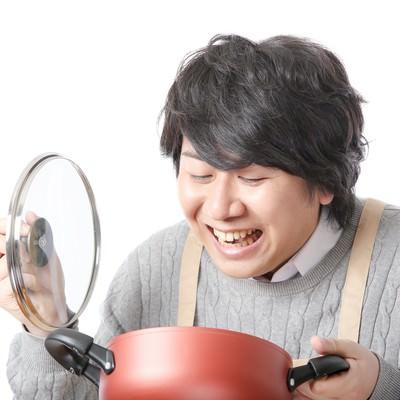 「我慢できずに鍋の蓋をあける食いしん坊」の写真素材