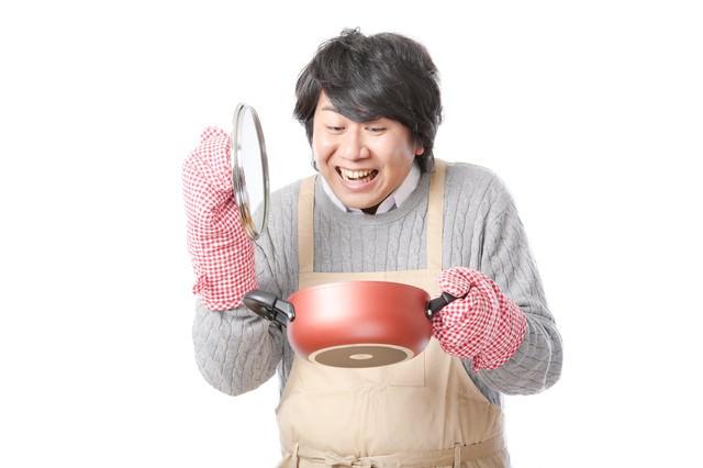 手料理に笑顔がこぼれるエプロン男子の写真