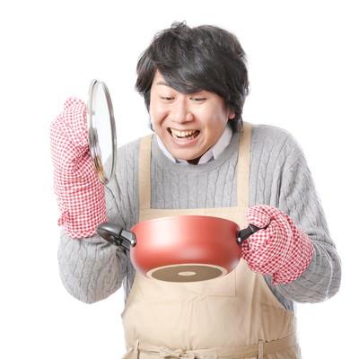 「手料理に笑顔がこぼれるエプロン男子」の写真素材