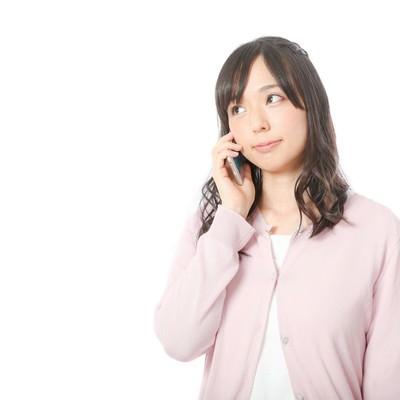 「親切丁寧な電話サポートに笑顔が溢れる女性消費者」の写真素材