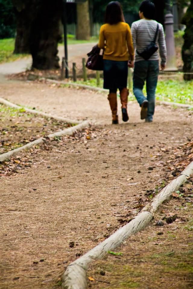 秋道を歩く恋人の写真