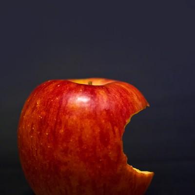 「片側をかじられた林檎」の写真素材