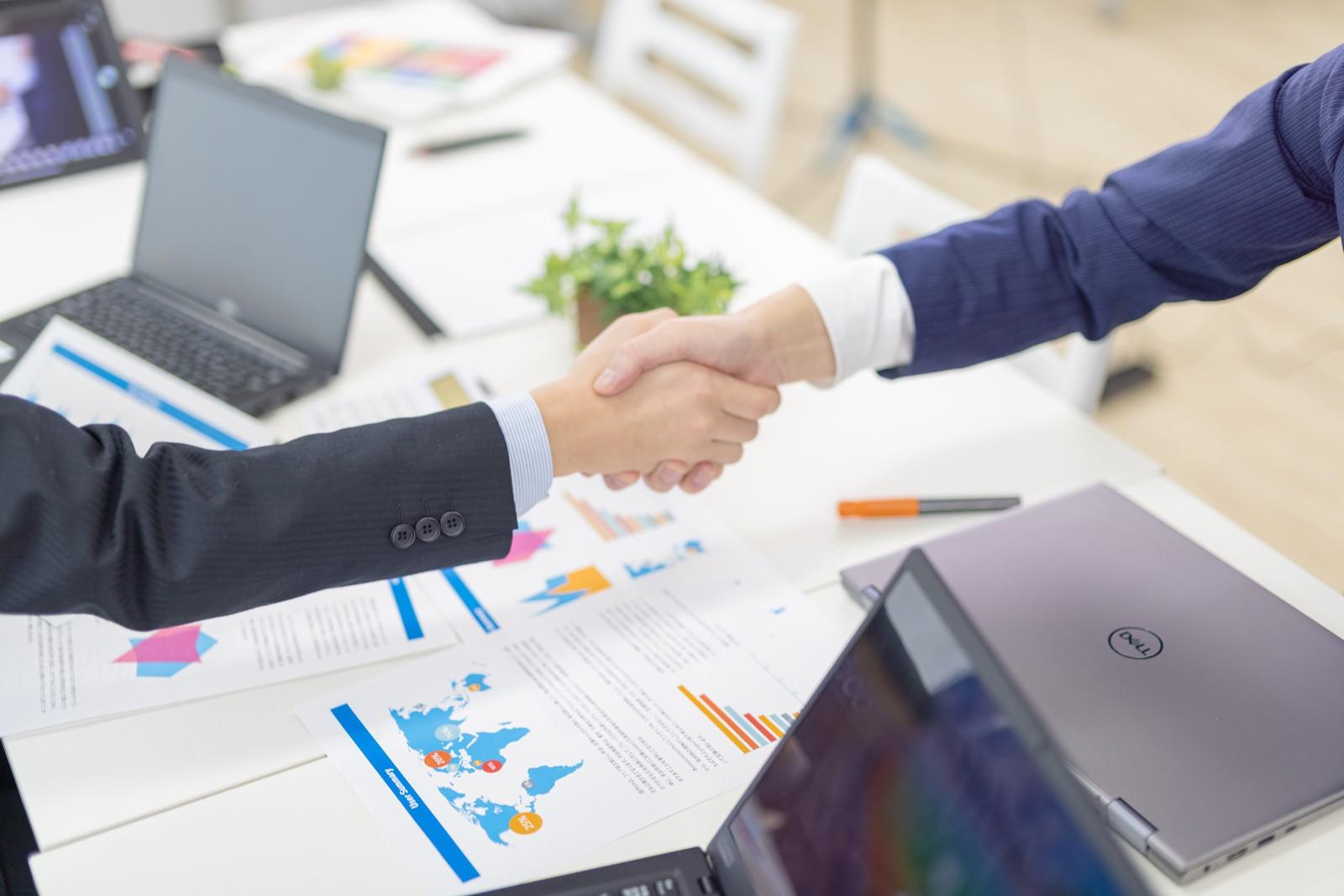 「会議後に握手を交わすビジネスマン」の写真