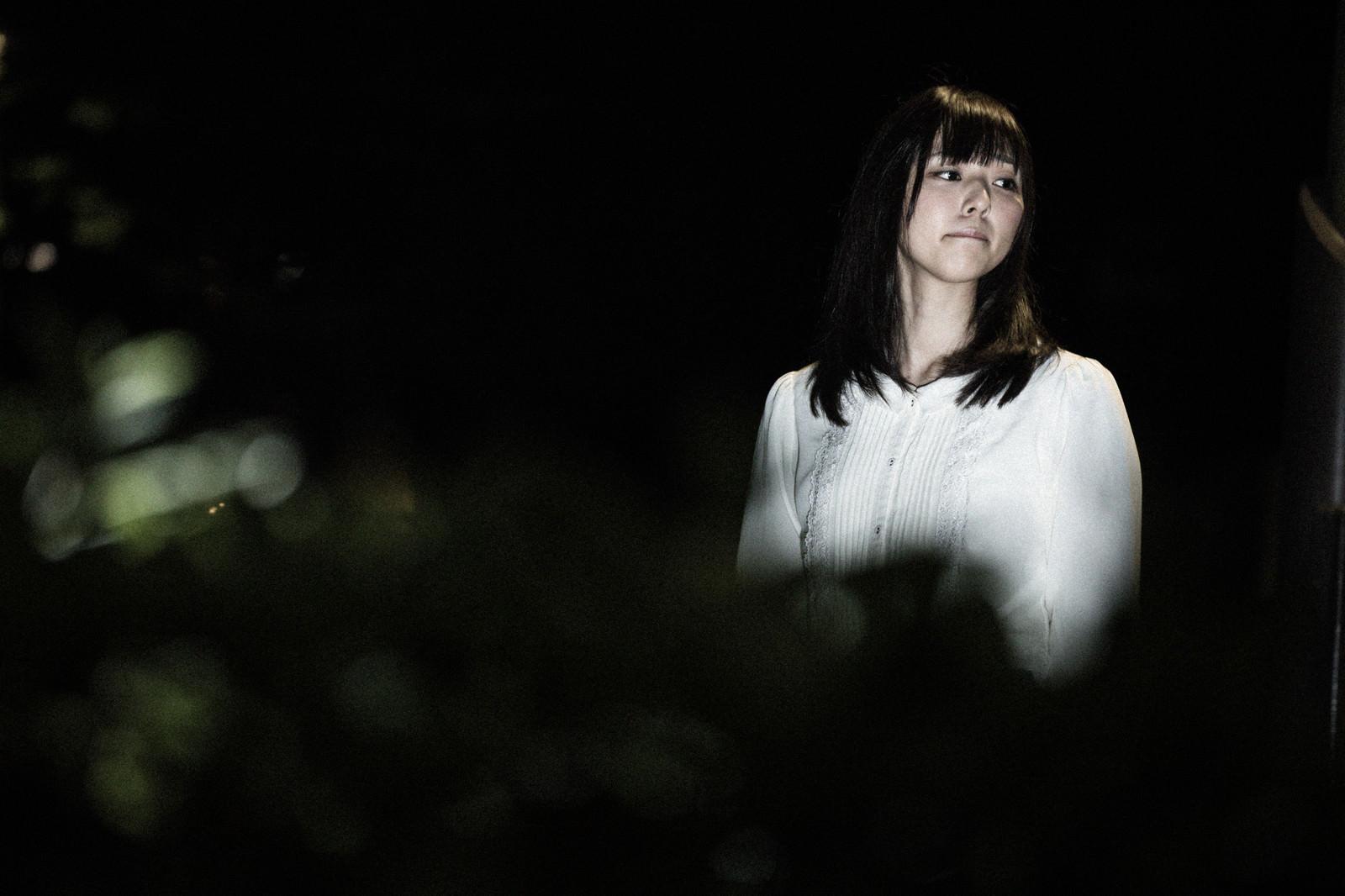 「怖がりながら夜道を歩く女性の姿」の写真[モデル:さとうゆい]