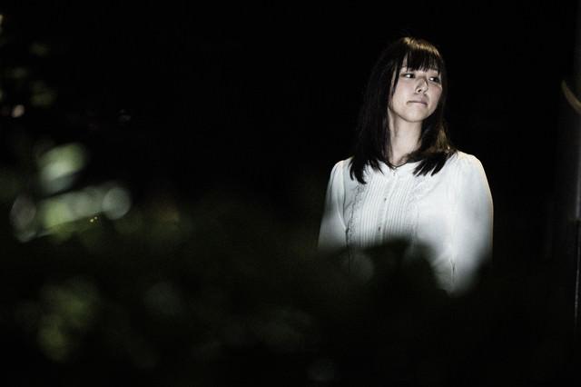 怖がりながら夜道を歩く女性の姿の写真