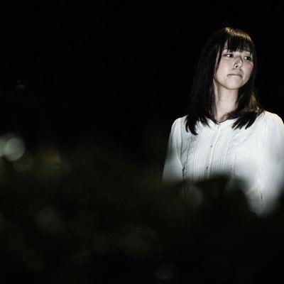 「怖がりながら夜道を歩く女性の姿」の写真素材
