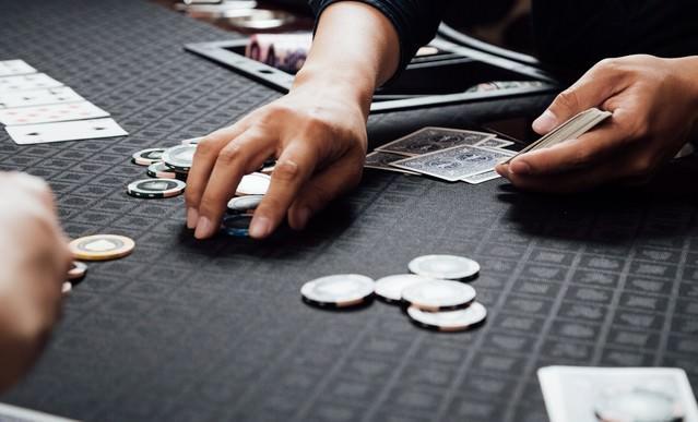 チップを回収するカジノディーラーの写真