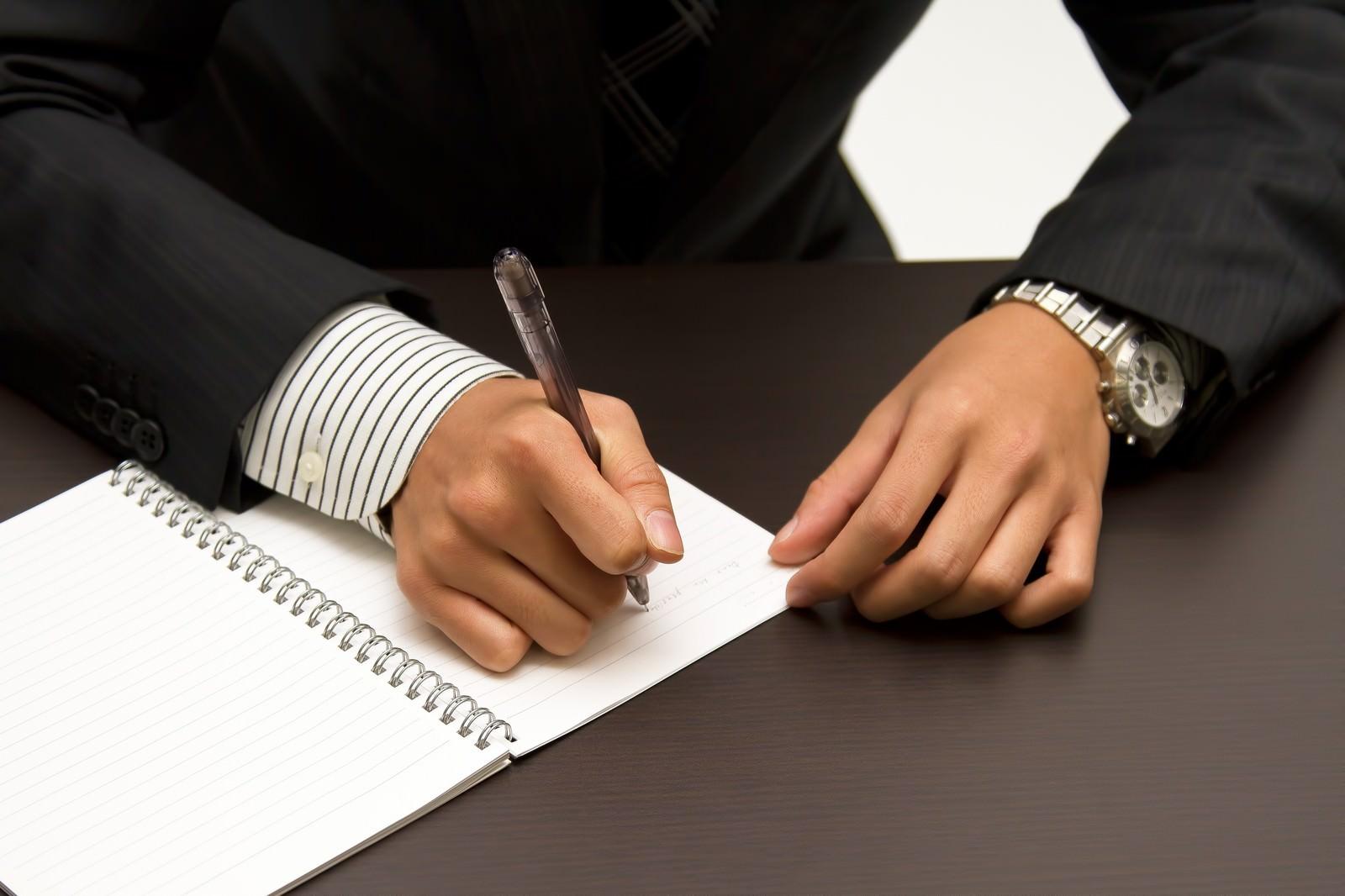 「ノートに書きこむビジネスマン」の写真