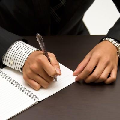 「ノートに書きこむビジネスマン」の写真素材