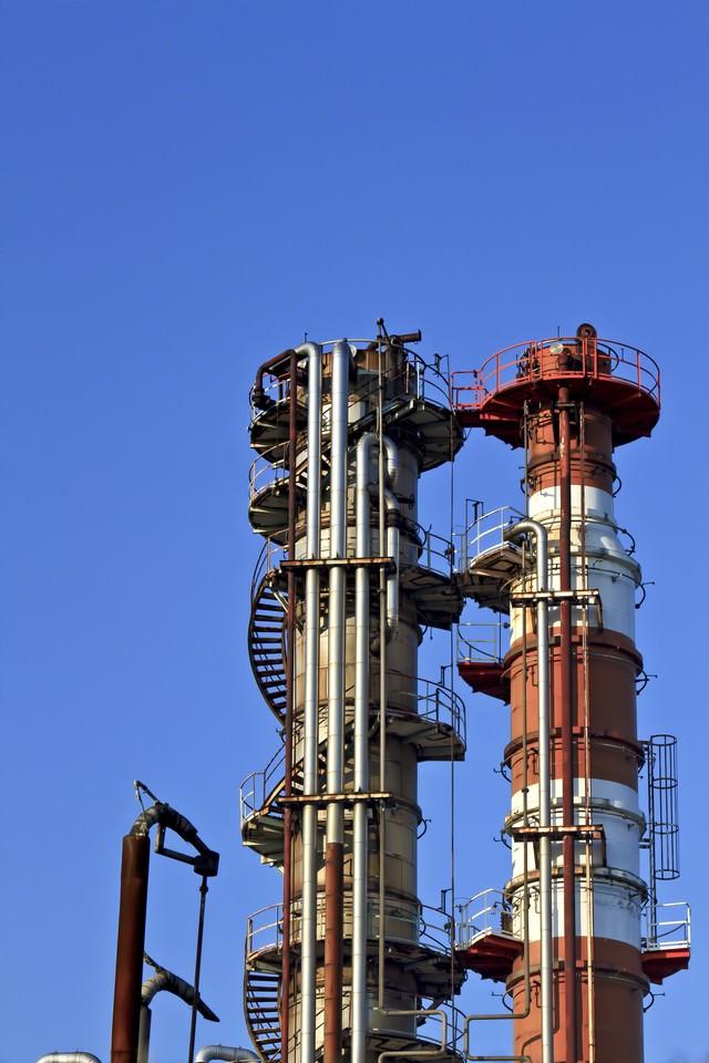 建ち並ぶ工場の煙突の写真
