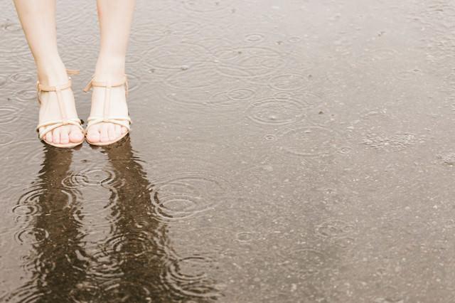 雨で足元がびしょ濡れの女性の写真