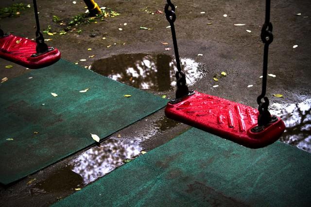 雨に濡れた赤いブランコの写真