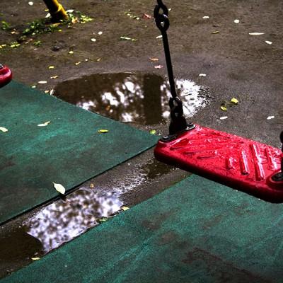 「雨に濡れた赤いブランコ」の写真素材