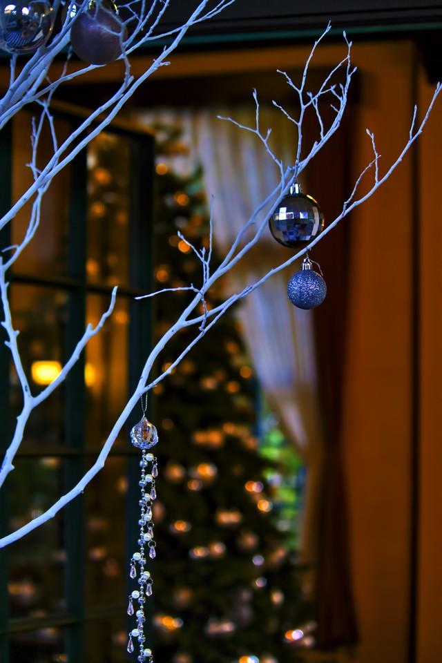白い飾りと奥に見えるツリーの写真
