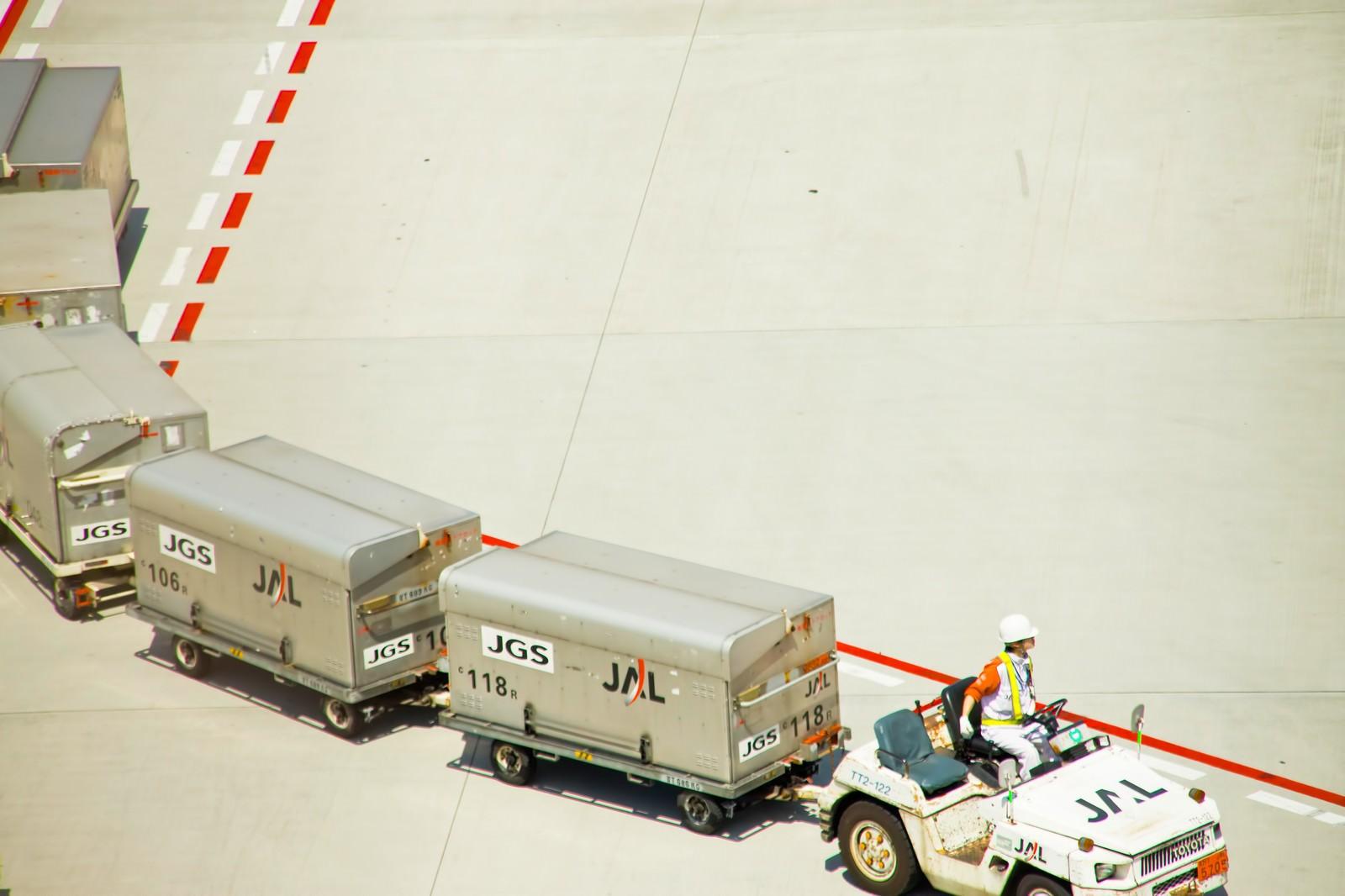 「空港のコンテナを運ぶ車」の写真