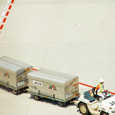 「空港のコンテナを運ぶ車」の写真素材