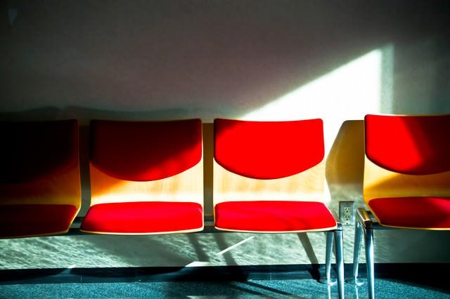 無機質な赤いベンチの写真