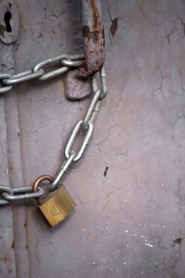 錆びた扉と南京錠の写真