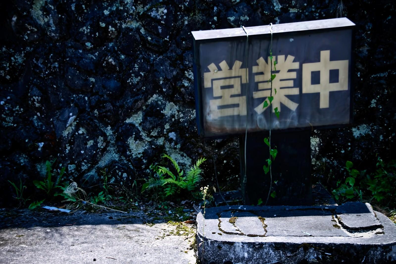 「朽ちた営業中の看板」の写真